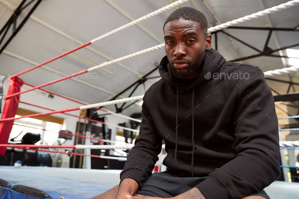 Portrait Of Male Boxer Wearing Hooded Sweatshirt In Gym Sitting On Boxing Ring - Stock Photo - Images