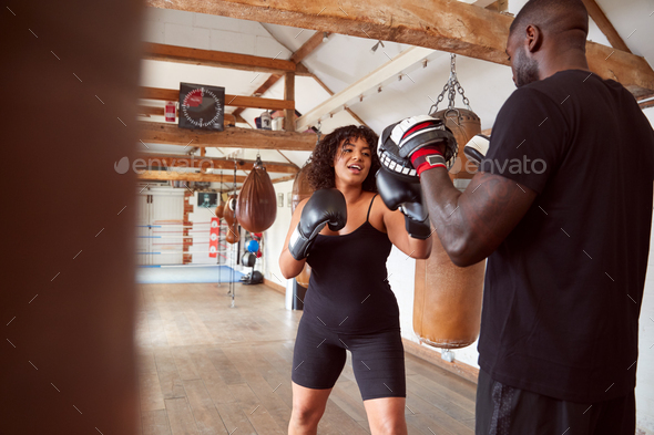Male Personal Trainer Sparring With Female Boxer In Gym Using Training Gloves - Stock Photo - Images