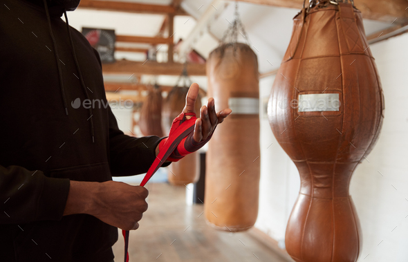 Close Up Of Male Boxer Training In Gym Putting Wraps On Hands Standing Next To Punching Bag - Stock Photo - Images