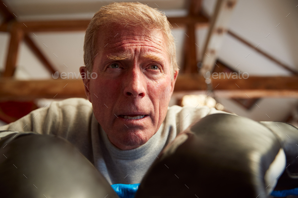 Senior Male Boxer In Gym Leaning On Ropes Of Boxing Ring Suffering From Heart Pain - Stock Photo - Images