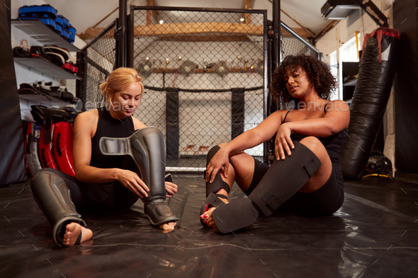 Two Female Mixed Martial Arts Fighters Putting On Protective Equipment Training In Gym - Stock Photo - Images