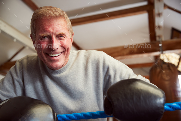 Smiling Senior Male Boxer In Gym Wearing Boxing Gloves Leaning On Ropes Of Boxing Ring - Stock Photo - Images