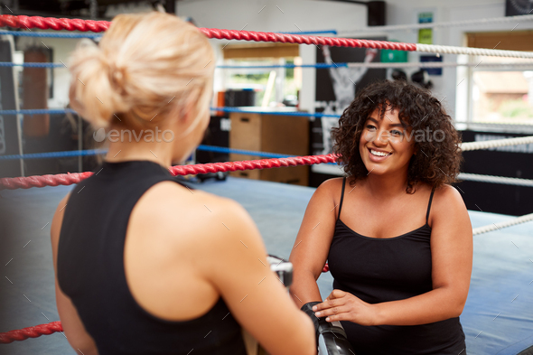Personal Trainer Helping Female Boxer In Gym To Put On Boxing Gloves In Gym - Stock Photo - Images