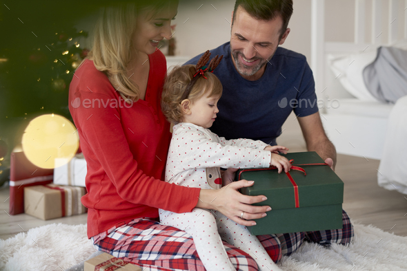Baby opening Christmas present with parents - Stock Photo - Images