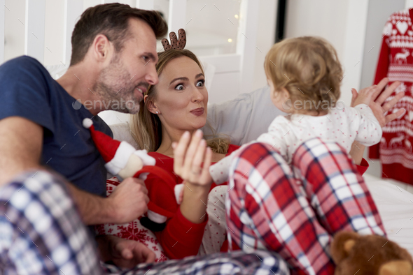 Baby with parents in bed during Christmas time - Stock Photo - Images