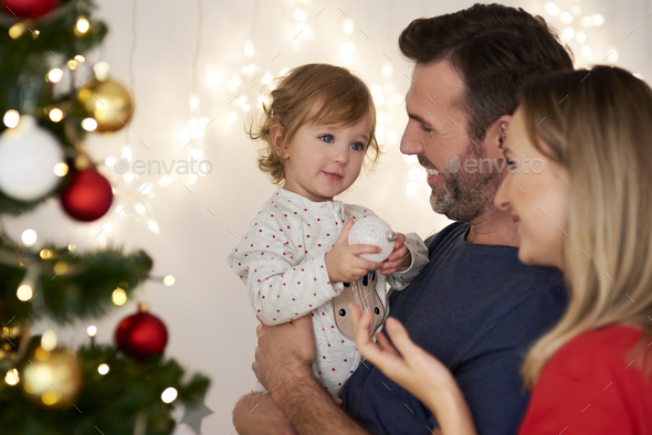 Parents with baby decorating Christmas tree - Stock Photo - Images