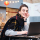 Pretty cheerful student girl with scarf happily studying on laptop in cafe on city street - PhotoDune Item for Sale