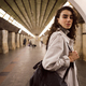 Beautiful girl in trench coat with backpack confidently looking in camera at subway station - PhotoDune Item for Sale