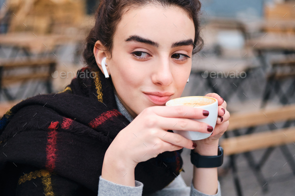 Pretty brunette girl with wireless earphones drinking coffee while wistfully looking away outdoor - Stock Photo - Images