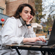 Attractive serious brunette girl in trench coat studying on laptop in cafe on city street - PhotoDune Item for Sale