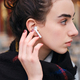 Side view of beautiful brunette girl with wireless earphones intently looking aside - PhotoDune Item for Sale