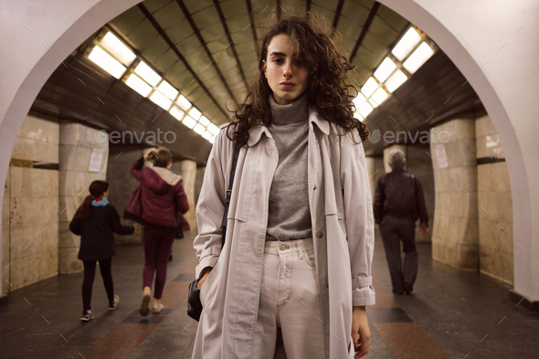Attractive girl in trench coat with backpack thoughtfully looking in camera at subway station - Stock Photo - Images