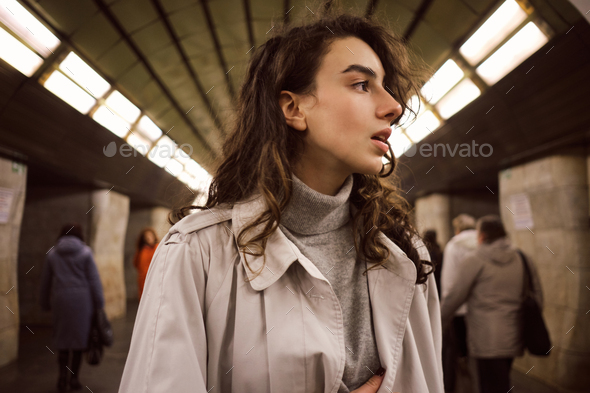 Portrait of pretty girl in trench coat thoughtfully looking away at metro station - Stock Photo - Images
