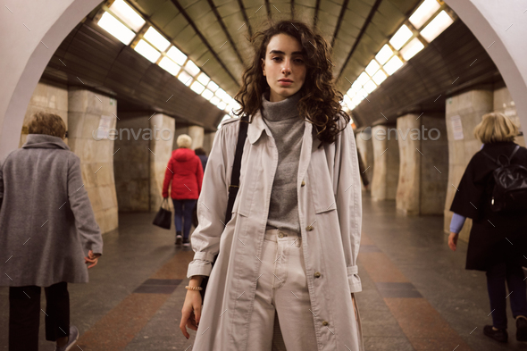 Pensive girl in trench coat with backpack dreamily looking in camera at subway station - Stock Photo - Images