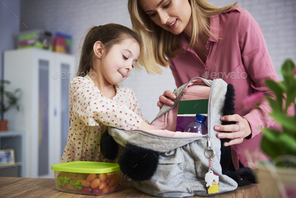 Young mum and daughter packing backpack for the school - Stock Photo - Images