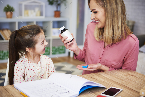Young mother giving pills to her daughter while doing homework - Stock Photo - Images