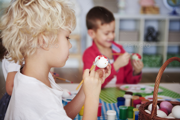 Side view of focused boy painting easter egg - Stock Photo - Images