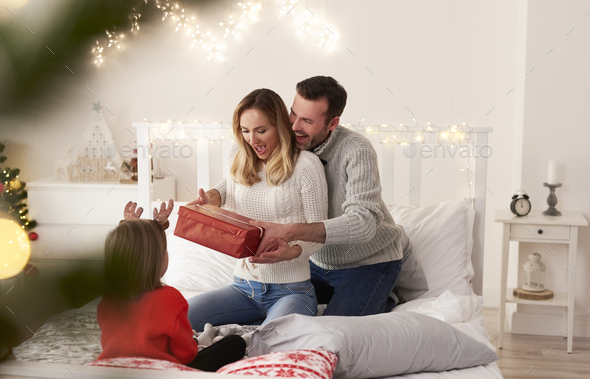 Excited family with gift spending Christmas morning in bed - Stock Photo - Images