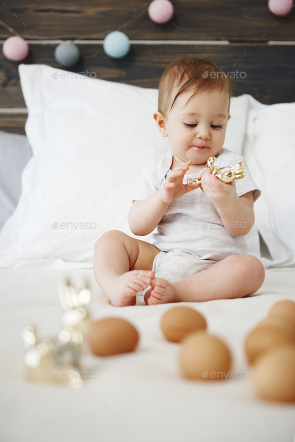 Baby playing with toy on the bed - Stock Photo - Images