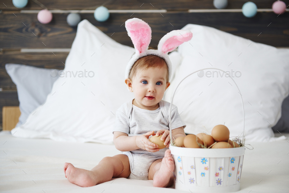 Portrait of adorable baby with bunny ears and easter basket - Stock Photo - Images
