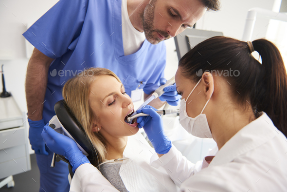 Young woman is getting treatment in dentist's office - Stock Photo - Images