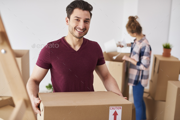 Smiling man moving into new home and unpacking his stuff - Stock Photo - Images