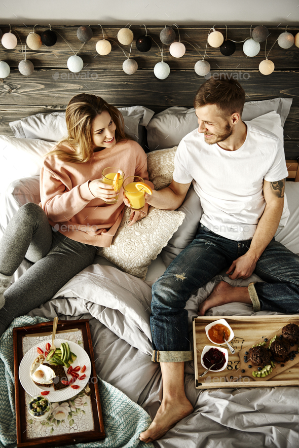 Happy couple having breakfast in bed - Stock Photo - Images