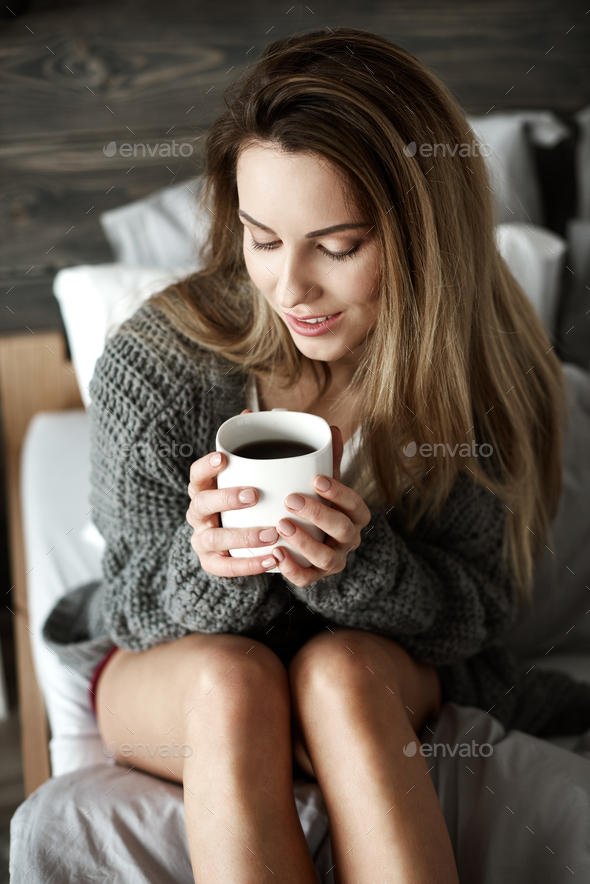 Pretty woman with coffee mug on bed - Stock Photo - Images