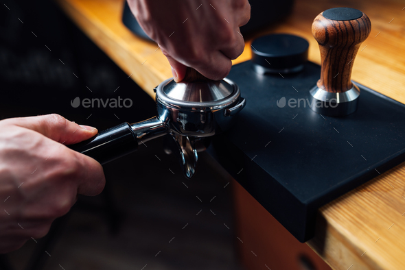 tempering coffee in portafilter on a dark background - Stock Photo - Images