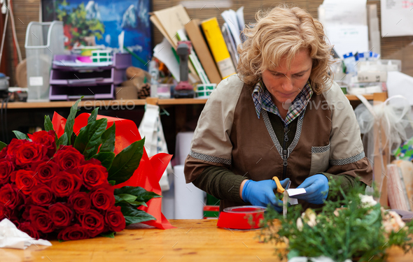 Florist with professional clothing in a nursery. - Stock Photo - Images