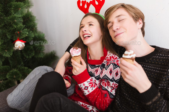 Portrait of young joyful couple having fun at home eating ice-cream at Christmas time - Stock Photo - Images
