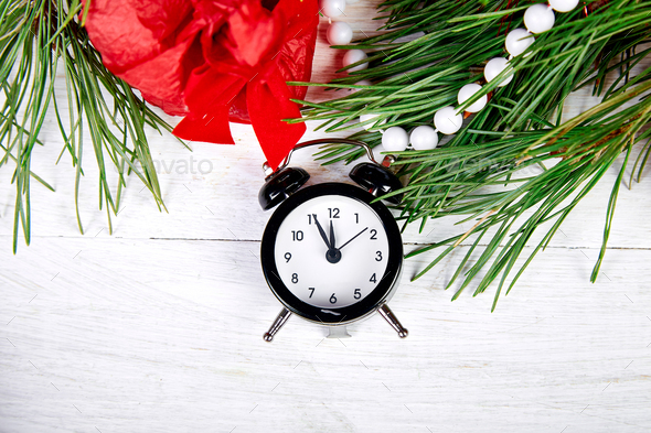 Black Alarm clock and fir tree branch, red christmas decorations - Stock Photo - Images