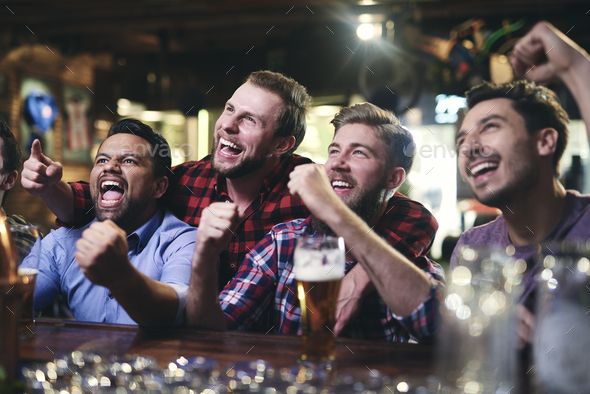 Excited football fans watching soccer in the pub - Stock Photo - Images