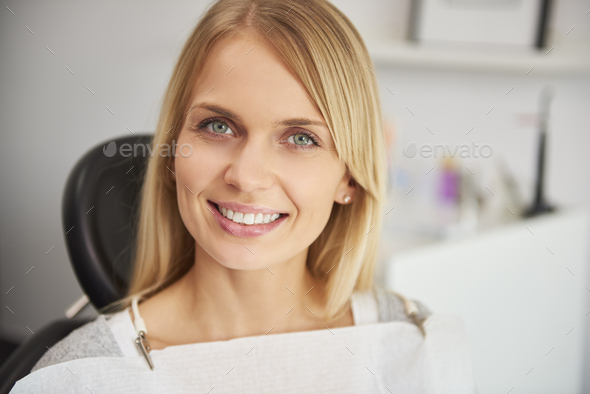Portrait of pleased and smiling woman in dentist's clinic - Stock Photo - Images