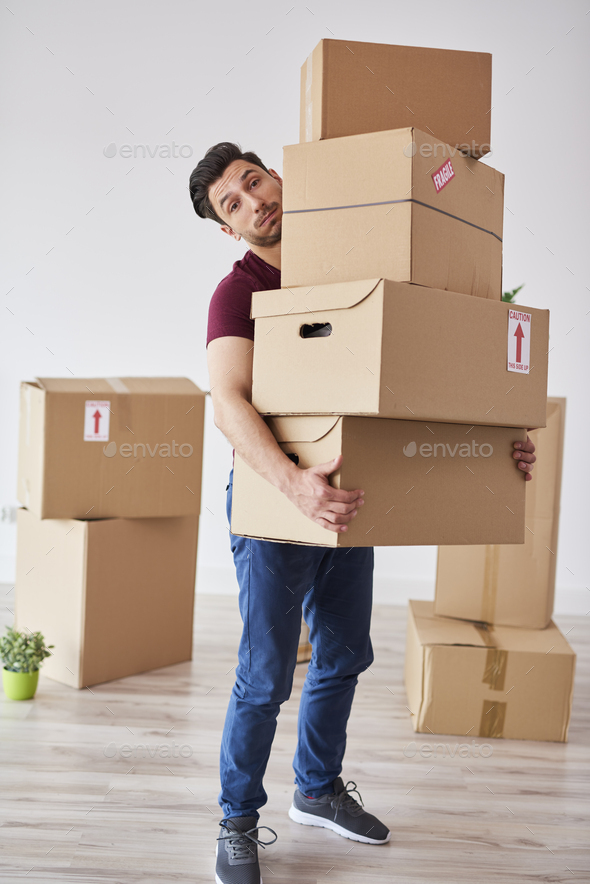 Portrait of man carrying stack of heavy cardboard boxes - Stock Photo - Images