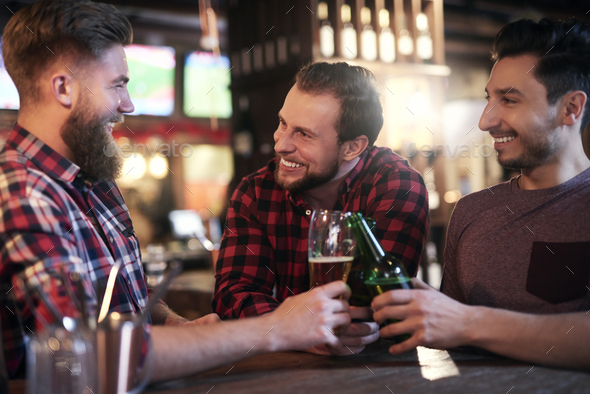 Three smiling men drinking beer in the pub - Stock Photo - Images