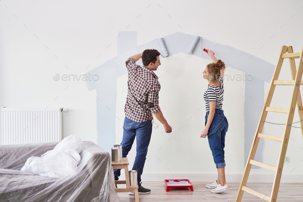 Young couple painting the interior wall in their new apartment - Stock Photo - Images