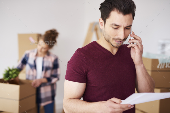 Man using cell phone in his new home - Stock Photo - Images
