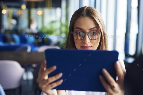 Focused, young woman using tablet - Stock Photo - Images