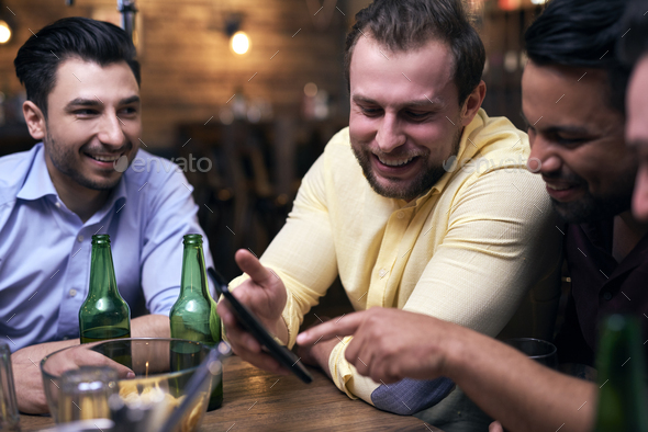 Men using mobile phone during meeting in the pub - Stock Photo - Images