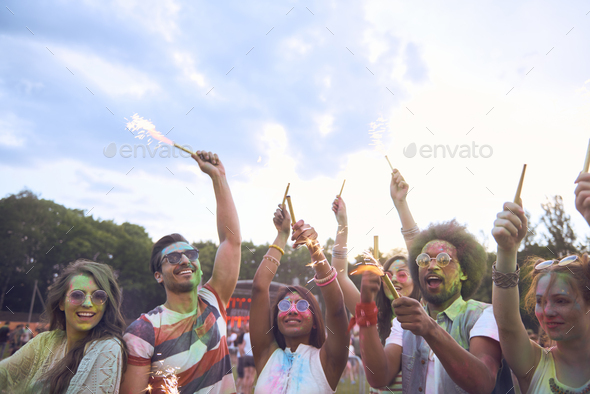 Friends with sparkler celebrating summer music festival - Stock Photo - Images