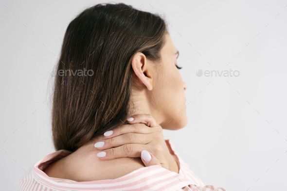 Rear view of young woman suffering from neck pain - Stock Photo - Images