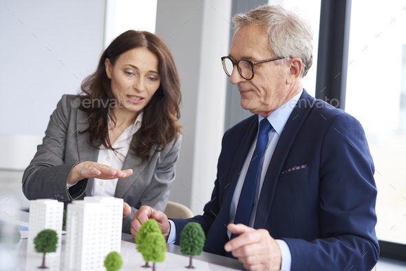 Business couple over architectural model - Stock Photo - Images