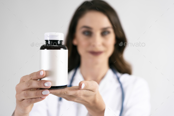 Doctor's hand holding medicament in bottle - Stock Photo - Images