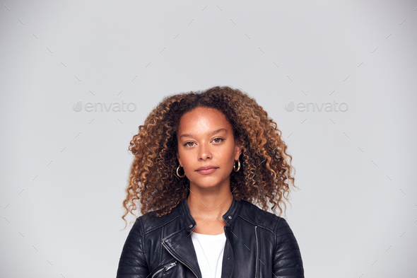 Studio Portrait Of Woman With Serious Expression Wearing Leather Jacket Looking At Camera - Stock Photo - Images