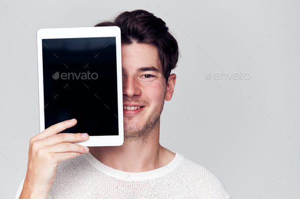 Studio Portrait Of Smiling Young Man Covering Face With Digital Tablet - Stock Photo - Images