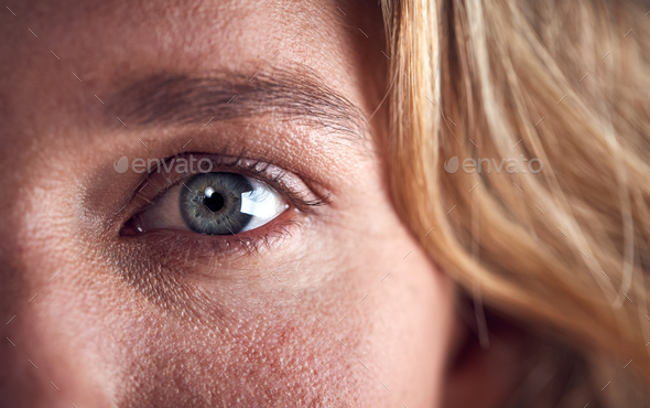 Close Up Of Eye Of Woman Looking Scared Against Black Studio Background - Stock Photo - Images