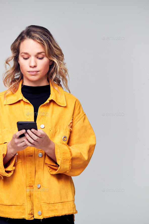 Studio Shot Of Causally Dressed Young Woman Using Mobile Phone - Stock Photo - Images