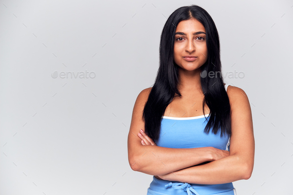 Studio Portrait Of Woman With Serious Expression And Folded Arms Looking At Camera - Stock Photo - Images