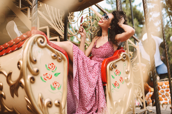 Pretty girl in sunglasses and dress holding lolly pop happily riding on carousel in amusement park - Stock Photo - Images
